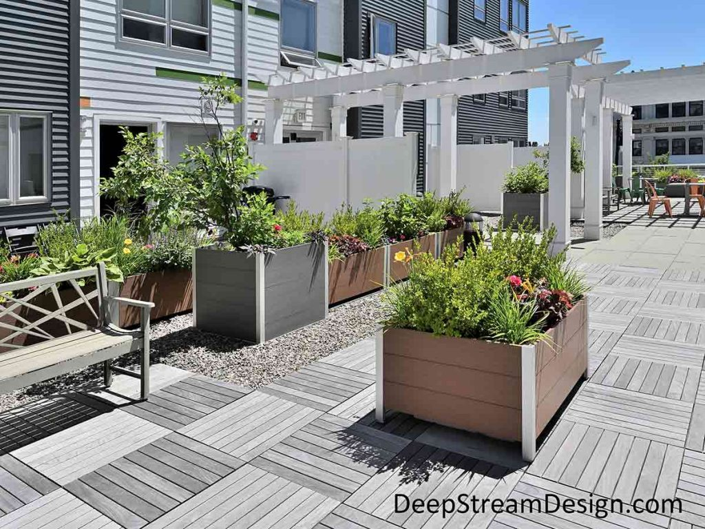 Dozens of Modern Square and Rectangular Commercial Wood Planters, in tan and dark grey colored labor saving no-maintenance recycled HDPE plastic lumber, create a green lushly landscaped common area patio on the roof deck of an urban workforce housing apartment complex.